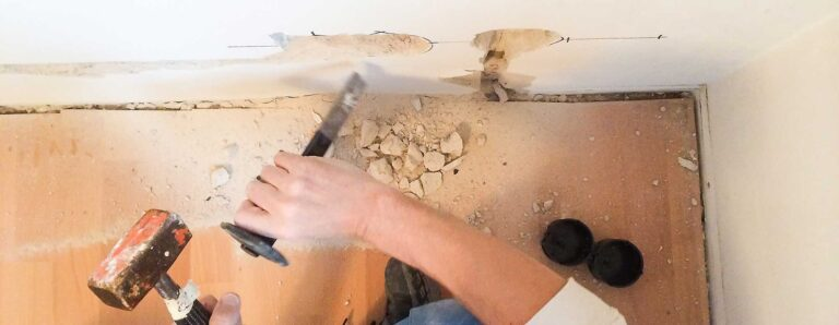 Ein Handwerker bereitet im Altbau die Wände zum Verlegen neuer Elektroleitungen und zum Setzen neuer Steckdosen vor.