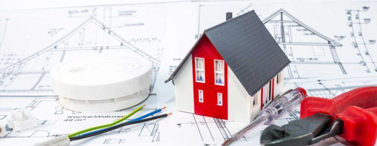 Für die Elektroplanung erforderlich: eine technische Zeichnung. Dargestellt werden außerdem ein Modell vom Haus, Elektrokabel, eine Lüsterklemme, ein Brandmelder und Werkzeug.