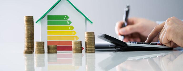 Mit einem Taschenrechner wird eine Ersparnis ausgerechnet und notiert. Es türmen sich Münzen vor einem Haus mit schematischer Darstellung von Energieeffizienzklassen.