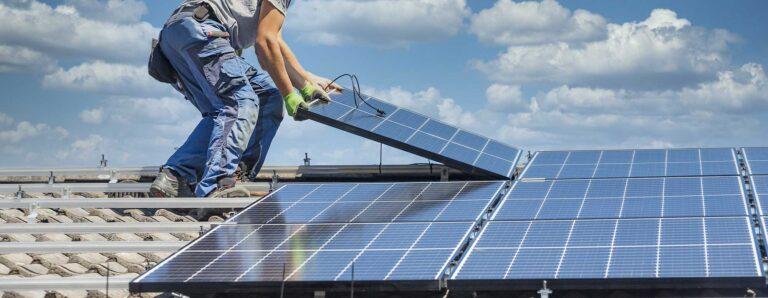 Handwerker installieren auf einem Dach Photovoltaikelemente für eine Heiz-PV Anlage.