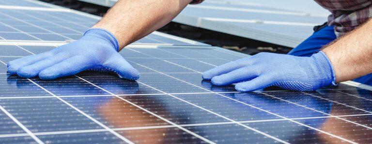 Ein Handwerker richtet sorgfältig die Elemente eine Photovoltaikanlage aus.