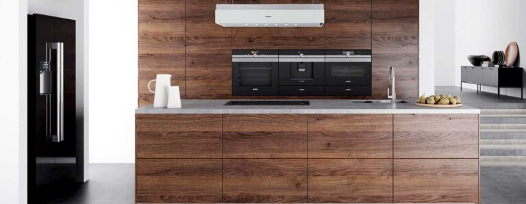 Moderne, neue, offene Küche in weißem Raum mit dunkelbraunen Holzfronten. Die Küche ist ausgestattet mit folgenden elektrischen Hausgeräten: Kühlschrank, Ofen, Kaffeeautomat, Mikrowelle und Kochfeld.